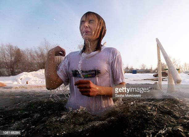 Russian lady an Orthodox believer crosses herself in the icy water of a local river as air temperature is minus 10 Celsius during traditional...