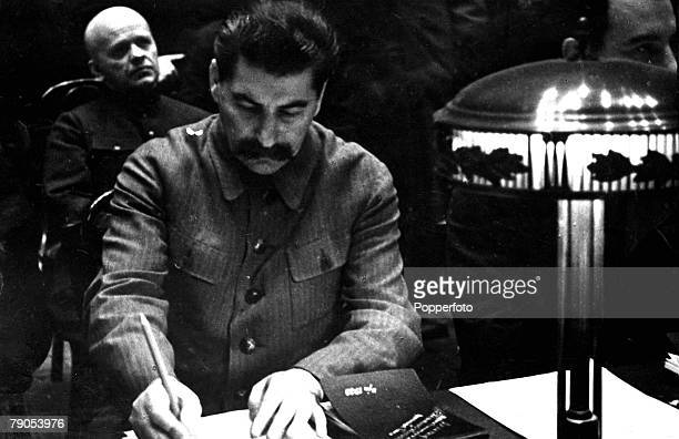 Russian Leader of the Communist party Josef Stalin writing as he sits at a desk