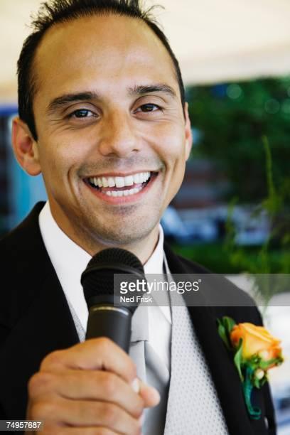 Russian man in tuxedo holding microphone