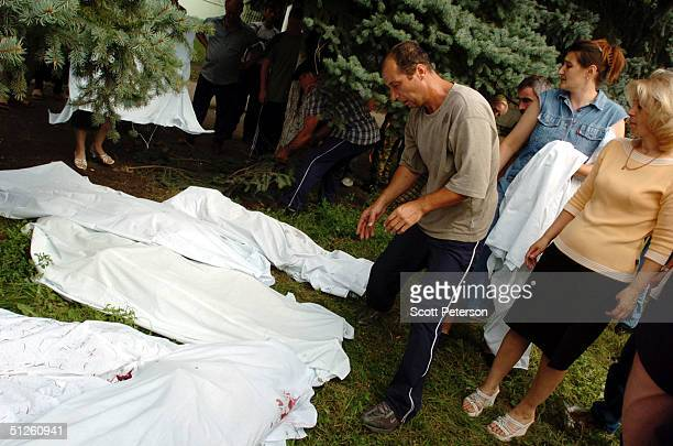 Russian man stands over bodies covered with sheets near a school September 3 2004 in Beslan Russia More than 200 people were reportedly killed and at...