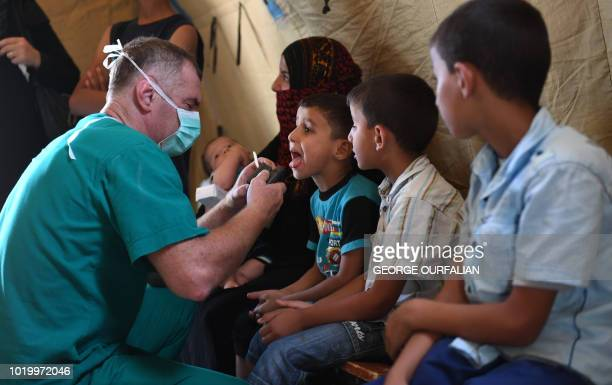 A Russian medic checks A Syrian child in a tent set up at the Abu Duhur crossing on the eastern edge of Idlib province on August 20 2018 Civilians...
