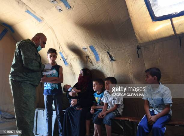 A Russian medic checks Syrians in a tent set up at the Abu Duhur crossing on the eastern edge of Idlib province on August 20 2018 Civilians are...
