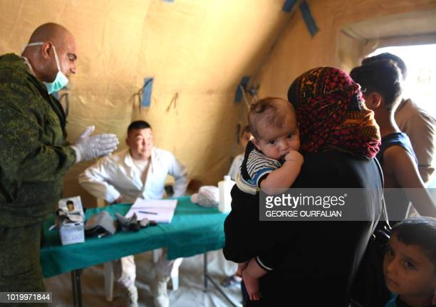 Russian medics check Syrians in a tent set up at the Abu Duhur crossing on the eastern edge of Idlib province on August 20 2018 Civilians are coming...