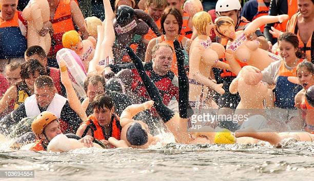 Russian men and women participate in the 'Bubble Baba Challenge' blowup sex doll swimming race on the river Vuoksa in Losevo village some 110 kms...