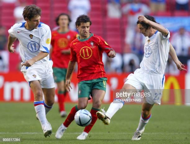 Russian midfielder Yevgeny Aldonin kicks the ball in front of his teammate defender Dmitry Sennikov and Portugal's forward Sabrosa Simao 16 June 2004...