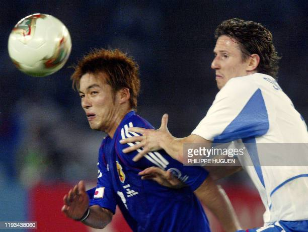 Russian midifielder Alexei Smertin tries to run by Japanese forward Atsushi Yanagisawa during the Group H first round match Japon/Russia of the 2002...