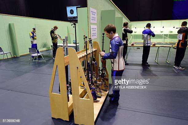Russian Mikhail Azarenko prepares his rifle at the test range of the running target category in AUDI Arena of Gyor on February 26 2016 prior to their...