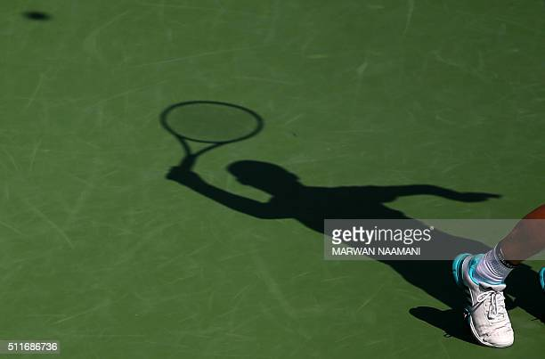Russian Mikhail Youzhny's shadow is seen on the court as he returns the ball to Tunisian Malek Jaziri during their ATP tennis match on the first...