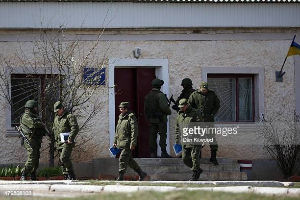 Russian military commanders leave a Ukrainian military base with paperwork on March 19 2014 in Perevalnoe Ukraine Russia's Constitutional Court ruled...