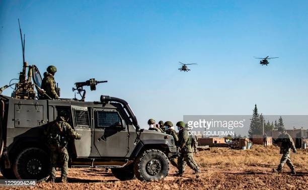 Russian military helicopters fly by soldiers and military vehicles during a joint Russian-Turkish patrol in the eastern countryside of the town of...