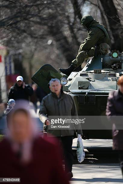 Russian military man sits on top of a Russian military personnel carrier outside a Ukrainian military base on March 18 2014 in Simferopol Ukraine...