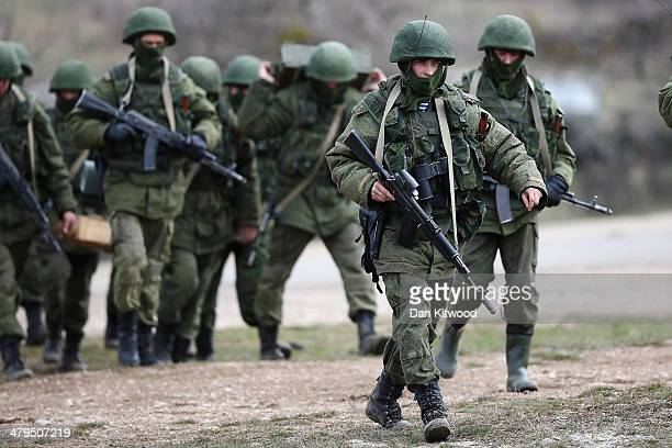 Russian military personnel move towards a Ukrainian military base on March 19 2014 in Perevalnoe Ukraine Russia's Constitutional Court ruled...
