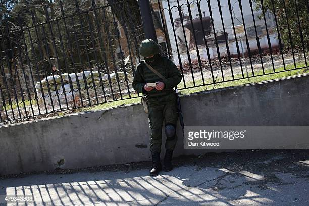 Russian military personnel reads a book outside a Ukrainian military base on March 18 2014 in Simferopol Ukraine Voters on the autonomous Ukrainian...