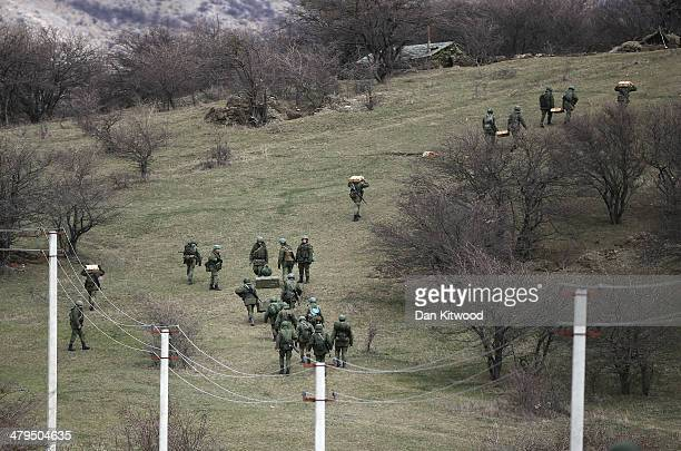 Russian military personnel take positions on a nearby hillside as they move towards a Ukrainian military base on March 19 2014 in Perevalnoe Ukraine...