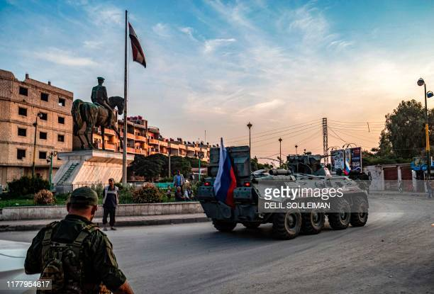 Russian military police armoured personnel carrier drives past an equestrian statue of Bassel al-Assad, the late brother of President Bashar al-Assad...