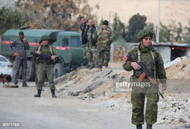 Russian military police members and Syrian government forces are seen at the Wafideen checkpoint on the outskirts of the Syrian capital Damascus...
