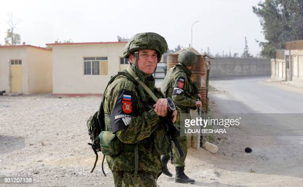 Russian military police members stand guard at the Wafideen checkpoint on the outskirts of the Syrian capital Damascus neighbouring the rebelheld...