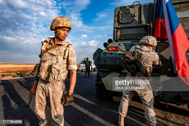 TOPSHOT Russian military police members stand outside an armoured personnel carrier along a road in the countryside near the northeastern Syrian town...