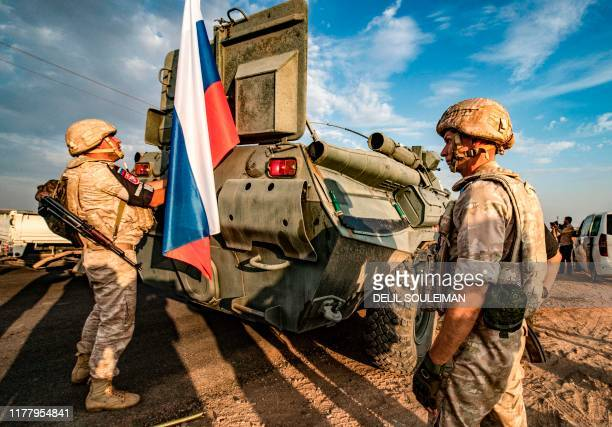 Russian military police members stand outside an armoured personnel carrier along a road in the countryside near the northeastern Syrian town of...