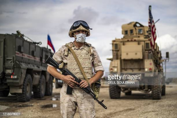 A Russian military police stands next to Russian and US military vehicles along the M4 highway by the town of Tal Tamr on May 25 as they monitor the...