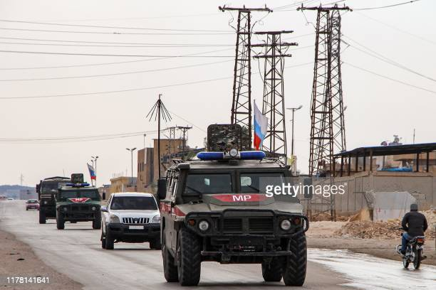 Russian military police vehicles drive in a joint patrol with the Syrian Kurdish Asayish internal security forces in the town of Kobane, also known...