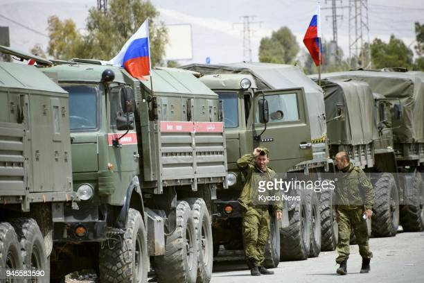 Russian military police walk beside trucks near the Eastern Ghouta city of Douma a suburb of the country's capital Damascus on April 12 2018 ==Kyodo