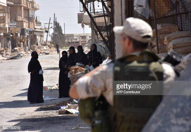A Russian military policemen stands guard as displaced Syrian women who are staying at a temporary shelter in Jibrin on the outskirts of Aleppo...