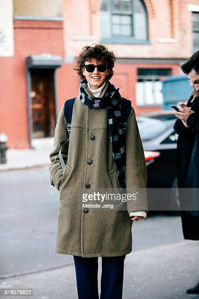 Russian model Alyosha Kovaleva exits the Suno show at Pier 59 in a blue scarf and an olive green coat with buttons during New York Fashion Week...