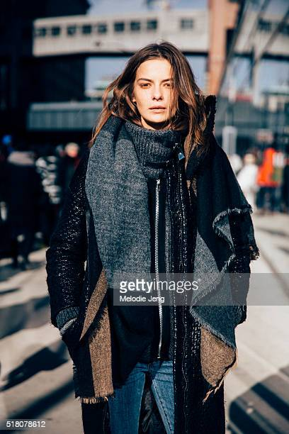 Russian model Dasha Denisenko exits the Tibi show at Skylight 60 Tenth in a black jacket with an oversized knit collar and a wool and cashmere scarf...