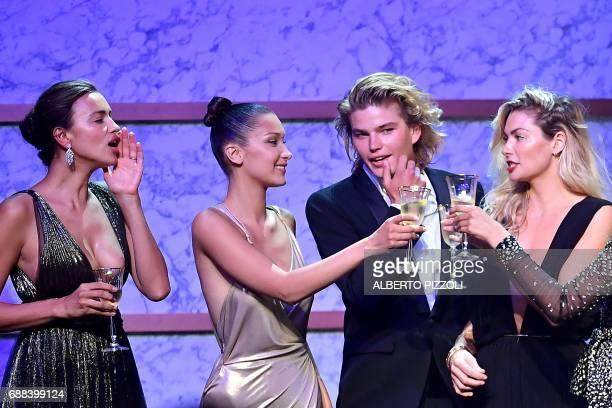 Russian model Irina Shayk US model Bella Hadid Australian model Jordan Barrett and Australian model Jessica Hart conduct an auction during the...