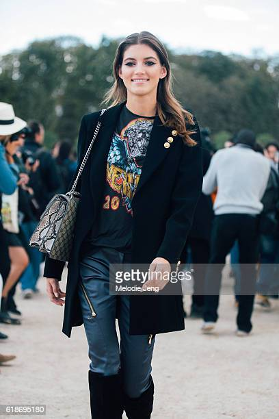 Russian model Valery Kaufman wears a black blazer leather pants a band tshirt and Gucci purse after the Elie Saab show at the Tuileries on October 01...