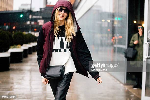 Russian model Zlata Semenko wears a black and red jacket a DKNY black and white logo sweatshirt a black purse and leather pants in the snow after the...