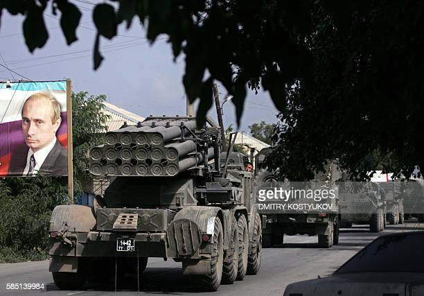 Russian multiple rocket launchers Uragan passes a banner featuring a portrait of Russian Prime Vladimir Putin as they leave South Ossetian capital...