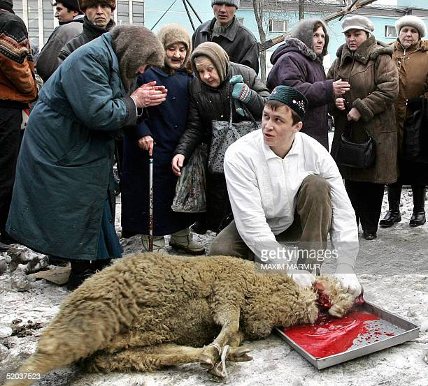Russian Muslim slaughters a sheep to mark the first day of the Moslim feast of Eid alAdha as Muscovites look at him outside the main Mosque in Moscow...