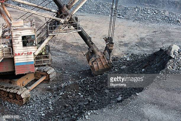 A Russian national flag sits on the side of an excavator as it collects iron ore from the open pit of the Stoilensky GOK iron ore mine and processing...