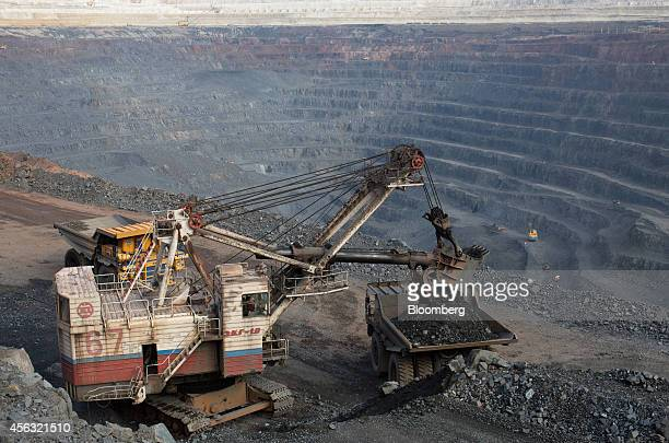 A Russian national flag sits on the side of an excavator as it loads iron ore from the open pit onto a waiting truck at the Stoilensky GOK iron ore...