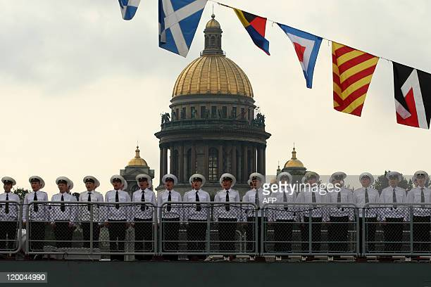 Russian Navy sailors stand on the deck of their ship during a Navy Day parade rehearsal on Neva River in front of one of the city landmarks St...
