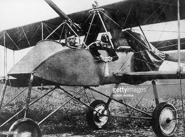 Russian officer fastens a bomb to the side of his warplane before take off, circa 1915.