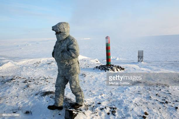 A Russian officer passes the state border sign on the shore of Barents Sea near the polar camp at Alexandra Land Island Franz Joseph Land Archipelago...