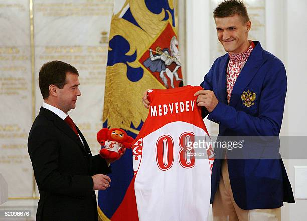 Russian Olympic basketball team player Andrei Kirilenko presents a Russian team jersey and a mascot to Russian President Dmitry Medvedev during a...