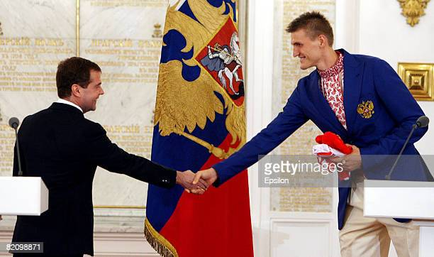 Russian Olympic basketball team player Andrei Kirilenko shakes hands with Russian President Dmitry Medvedev during a wellwishing ceremony for the...