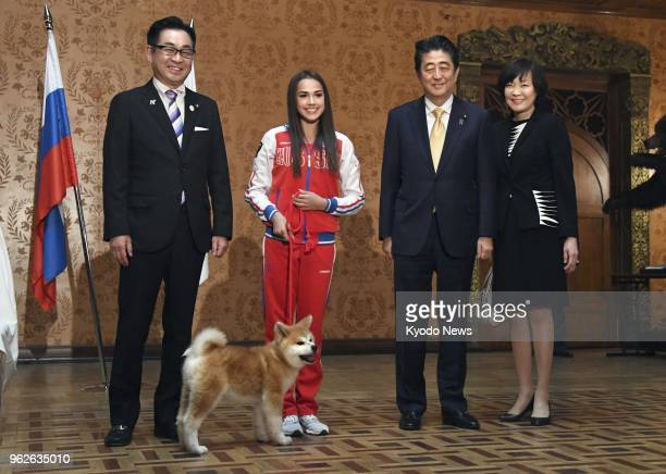 Russian Olympic figure skating champion Alina Zagitova poses beside an Akita puppy she received from a group preserving the Japanese dog breed at a...