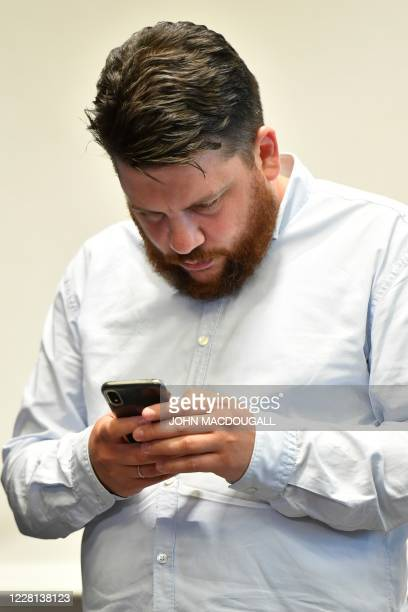Russian opposition figure Alexei Navalny's Chief of Staff, Leonid Volkov checks his phone at the end of a press conference with members of German...