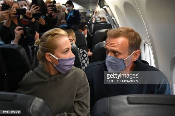 Russian opposition leader Alexei Navalny and his wife Yulia sit in a Pobeda airlines plane heading to Moscow before take-off from Berlin Brandenburg...