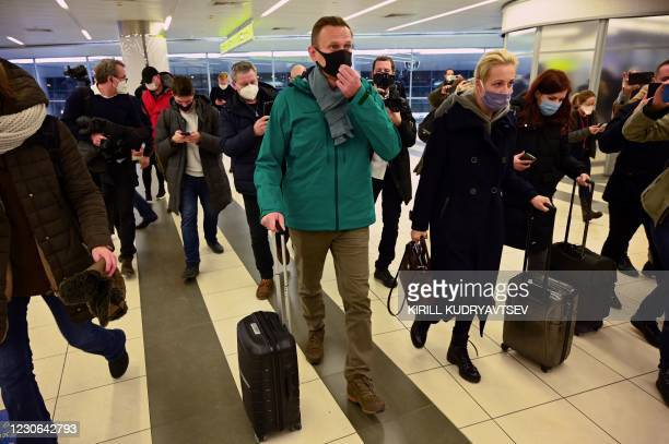 Russian opposition leader Alexei Navalny and his wife Yulia walk towards the passport control point at Moscow's Sheremetyevo airport upon the arrival...