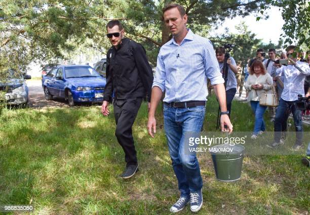 Russian opposition leader Alexei Navalny and his younger brother Oleg walks in the village of Naryshkino in the Oryol region south of Moscow on June...