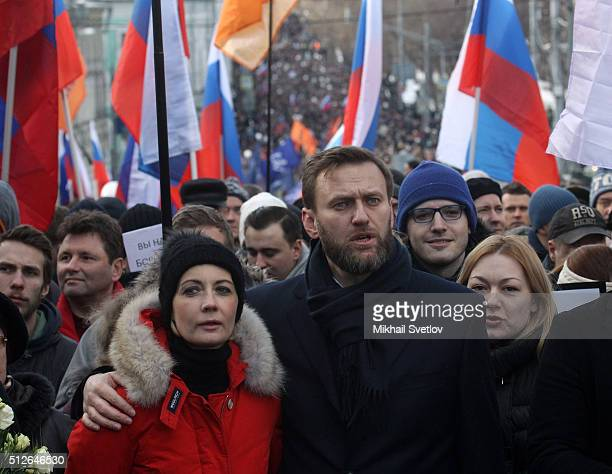 Russian opposition leader Alexei Navalny embraces his spouse Yulia Navalnaya attend a mass march marking the oneyear anniversary of the killing of...