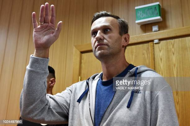 TOPSHOT Russian opposition leader Alexei Navalny gestures during his trial at a Moscow courthouse on August 27 2018 A Moscow court on August 27 2018...