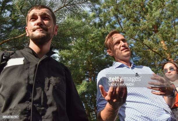 Russian opposition leader Alexei Navalny speaks as he stands next to his younger brother Oleg in the village of Naryshkino in the Oryol region south...