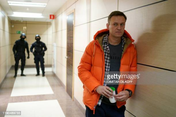 Russian opposition leader Alexei Navalny stands near law enforcement agents in a hallway of a business centre, which houses the office of his...